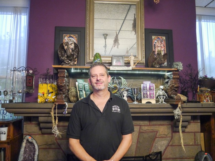 Man poses in front of fireplace and trinkets