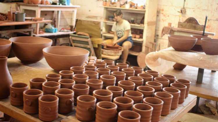 woman working at pottery wheel at Earthborn Studios, Inc. in Leeds