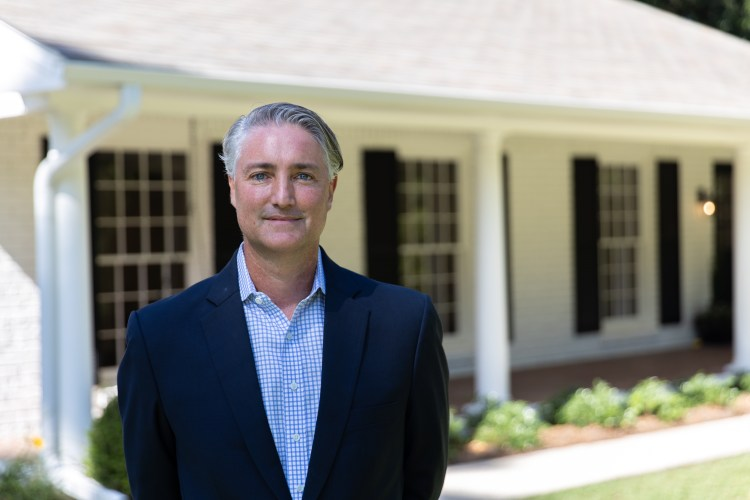 Michael Murphree of ARC Realty in front of a house for sale