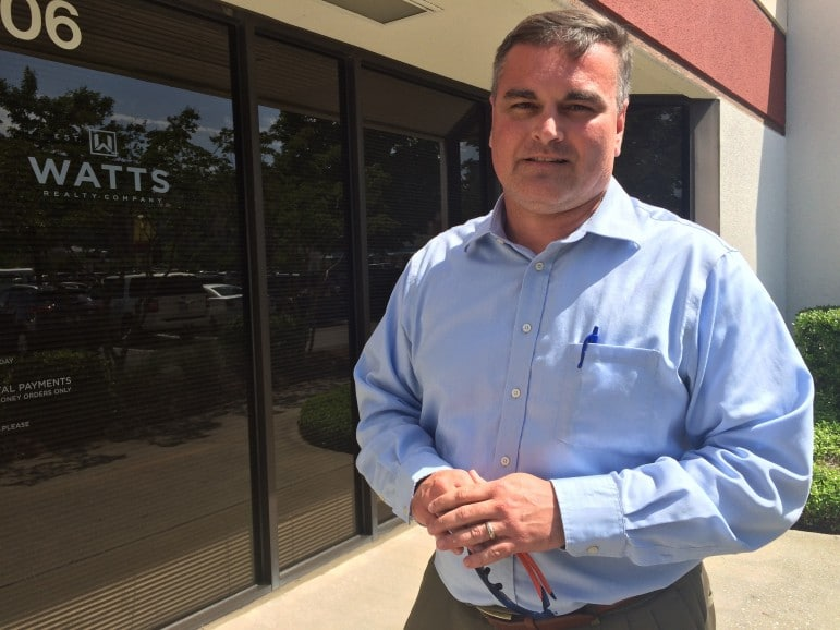 Chip Watts standing in front of a Watts Realty building