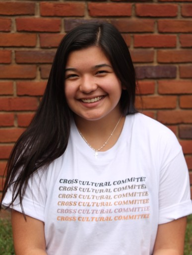 Photo of Lizbeth smiling wearing Cross Cultural Committee shirt for Hispanic Heritage Month