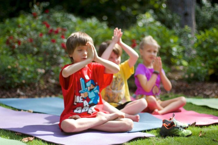 3 young children in restful yoga poses outside on colorful yoga mats