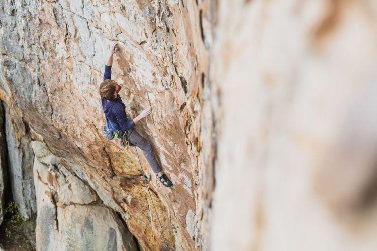 Man climbing up a rock wall outside - community sports in Birmingham