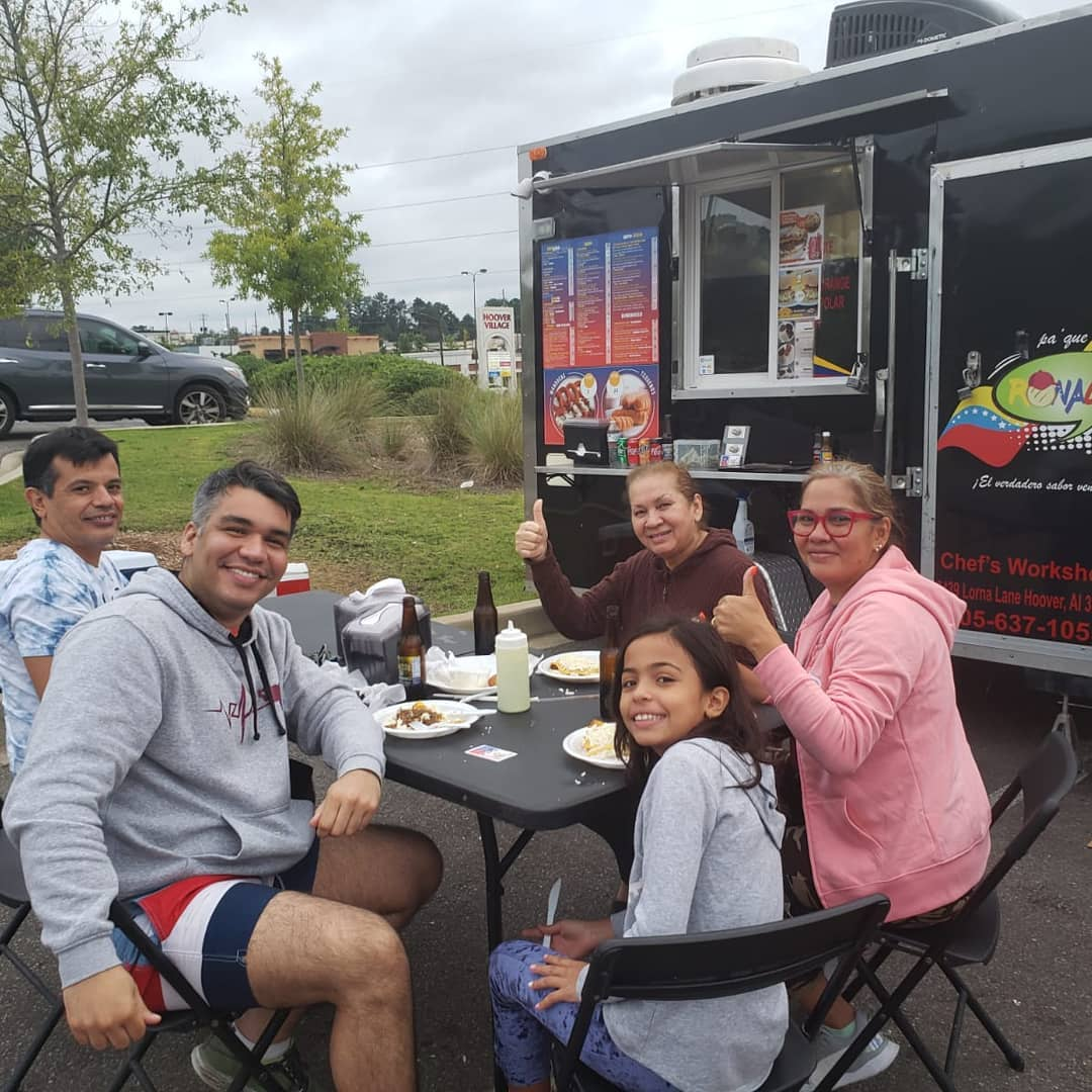 A smiling family sits outside of Pa'Que Ronald food truck