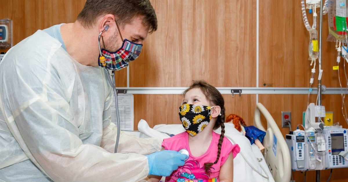 An Registered Nurse bonding with a pediatric patient at Children's of Alabama