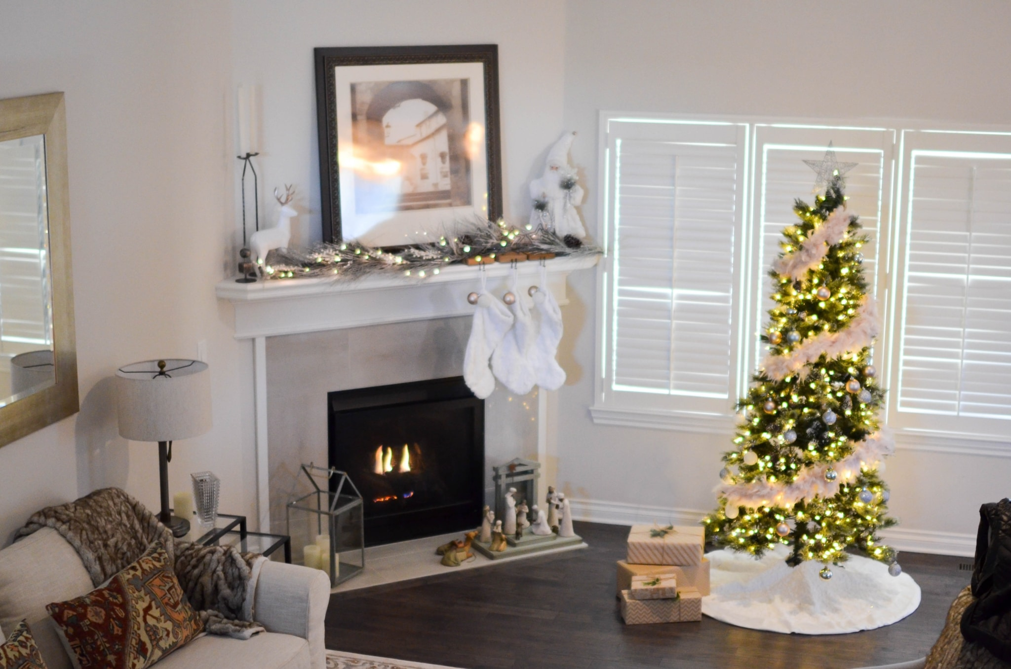 Christmas tree with string lights turned on near electric fireplace inside room