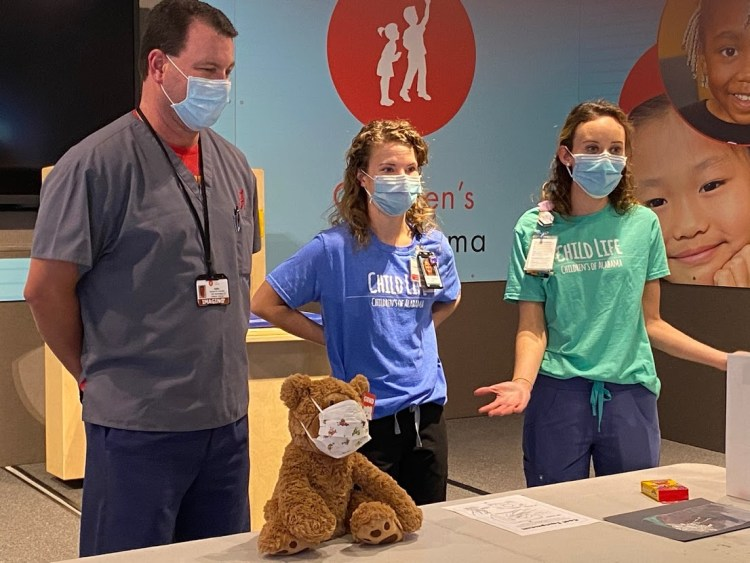 Three healthcare workers teach children how to put on a face mask.
