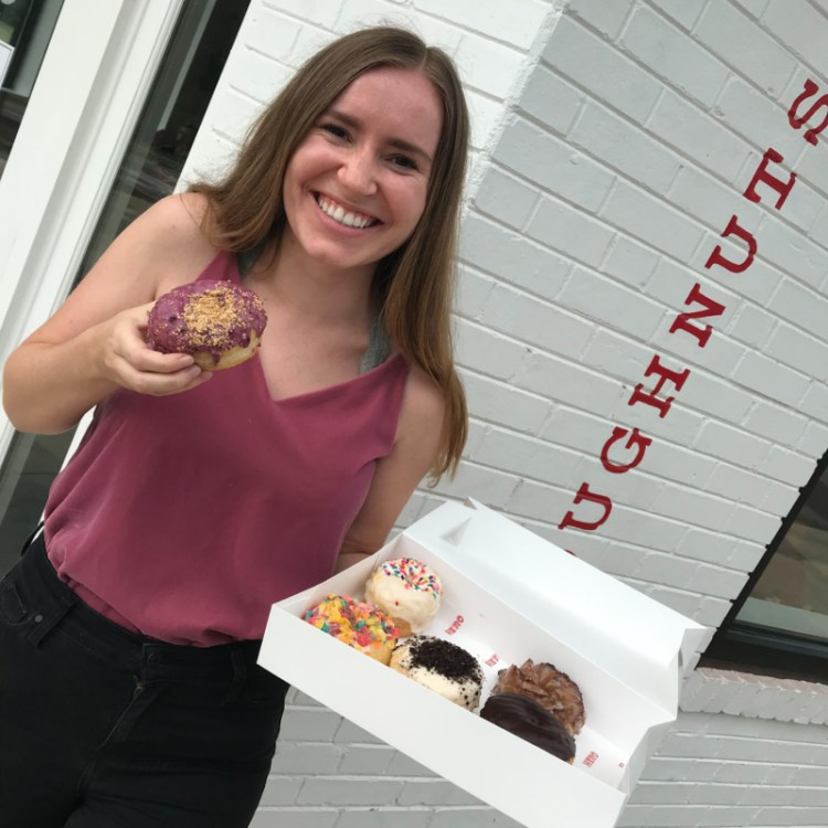 Cecilia holding up a donut from Hero Doughnuts for Bham Now