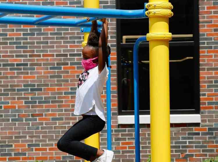little girl hanging from monkey bars