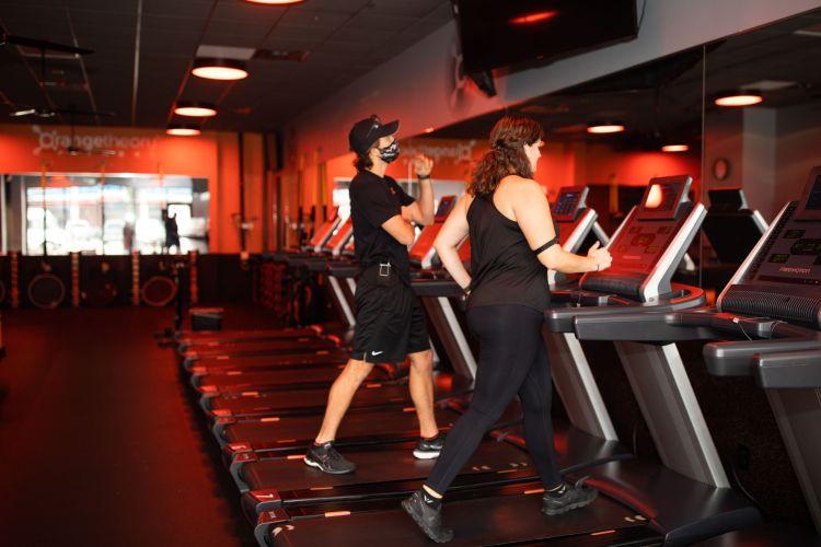 Orangetheory, coach and member on treadmill