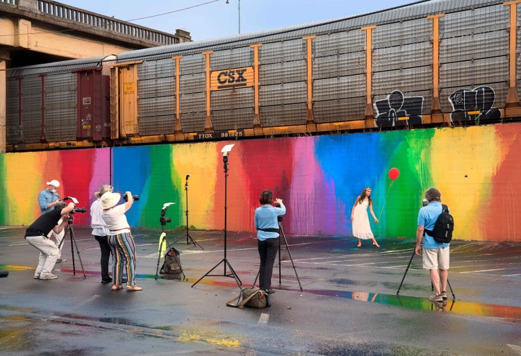 Flash photography class takes pictures of a student against a rainbow wall