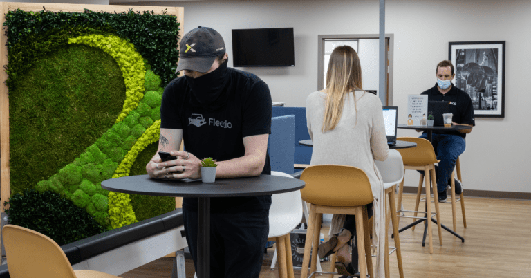 People sitting and standing at desks - Pelham's coworking space