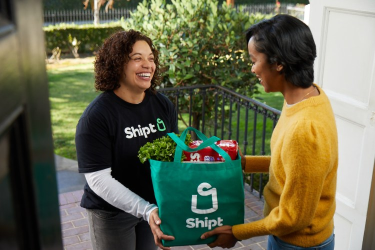 Woman in Shipt logo tshirt handing green grocery bag with items inside to woman standing in doorway.