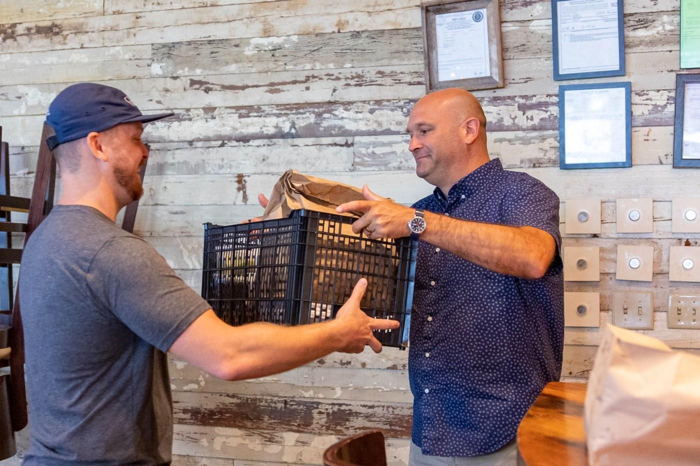 Little Donkey founder handing catering order to Brett Ables