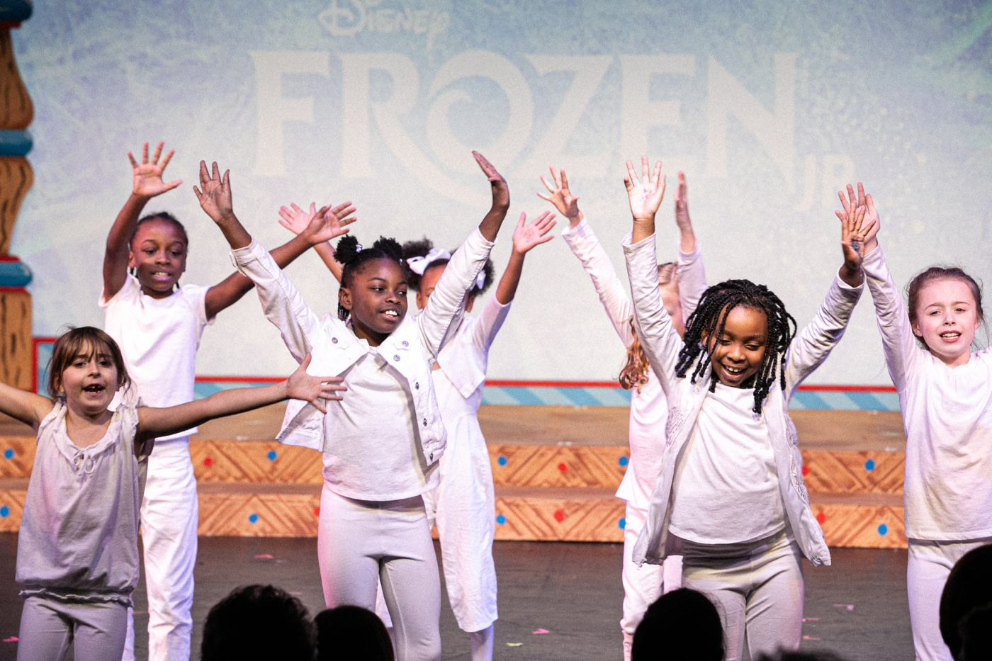 Children in white performing for a Red Mountain Theatre performance