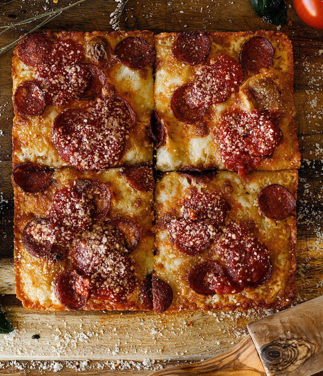 4 slices of square pepperoni pizza on a wood background sprinkled cheese.