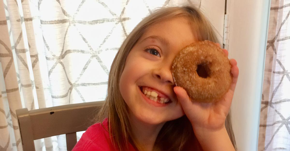 LIttle Girl looking through a donut