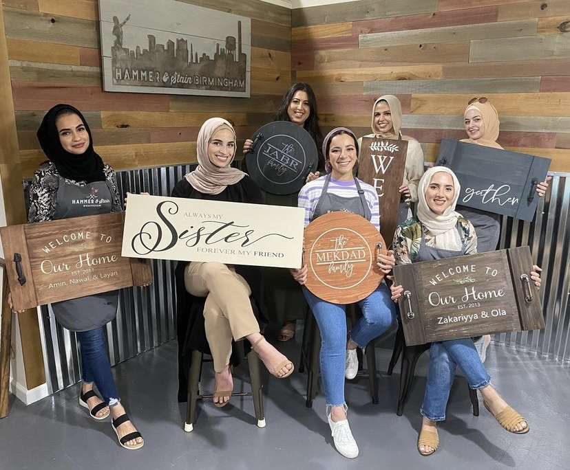 group of women holding pretty wooden signs