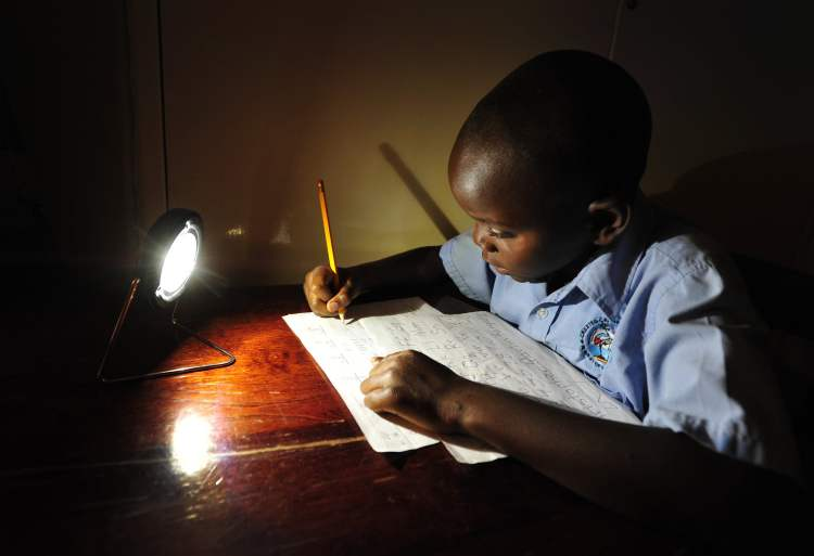 Socially Responsible Investing: A boy studies by light powered from solar panels as part of the Solar Aid Socially Responsible Project