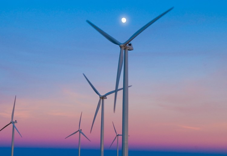 wind power turbines at sunset stand still because of curtailment due to lack of capacity on the electricity transmission network