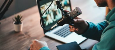 A,Man,Host,Streaming,His,Audio,Podcast,Using,Microphone,And
