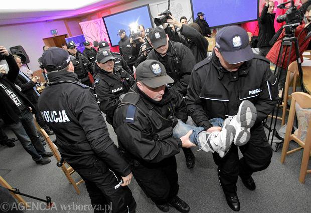 Policjanci wyprowadzają demonstrantów, którzy wdarli się do siedziby Państwowej Komisji Wyborczej i okupowali salę konferencyjną. Protestujący pod kierownictwem Ewy Stankiewicz i Grzegorza Brauna domagali się dymisji członków PKW. Warszawa, 20 listopada 2014 r.