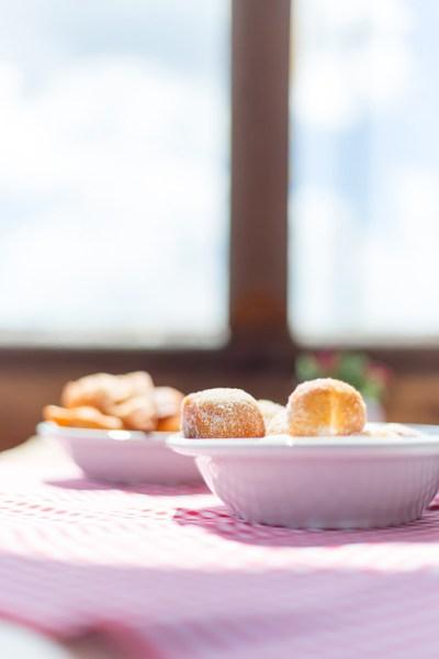 Janela ao fundo com céu azul em desfoque, mesa de café da tarde com mini sonhos dentro de pratos de servir em foco.