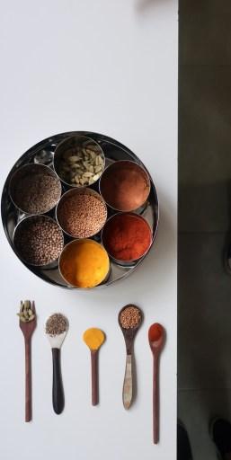 Vista superior de uma mesa branca com especiarias dentro de bowls e colheres alinhadas com especiarias dentro delas, sob a bancada.