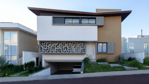Fotografia de arquitetura diurna: Casa com telhado invertido, volumes bem marcados e cobogó na fachada, fotografada à luz do dia. Isso evidencia os volumes da fachada.
