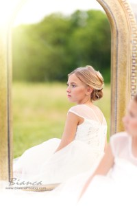 Young girl in white dress near outdoor mirror
