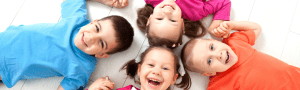 four children smiling on the ground