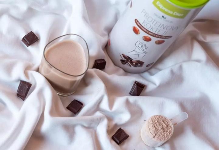 Čokoládovo-orieškový proteín pre vegánov s plnou odmerkou, naplneným pohárom a čokoláda