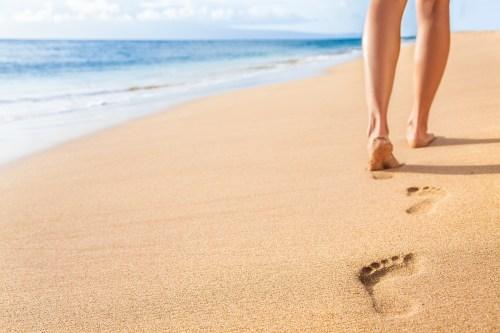 Beach travel - woman relaxing walking on sand beach leaving foot