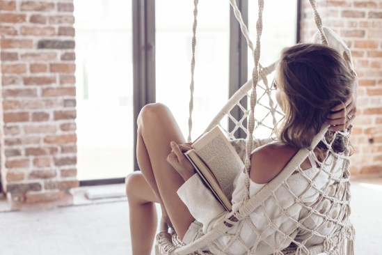 Young woman chilling at home in comfortable hanging chair. Girl