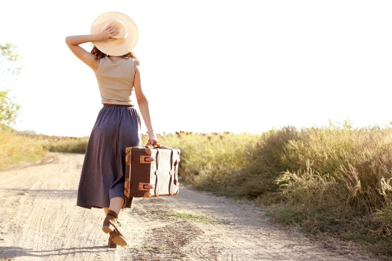 Young woman with suitcase walking along countryside road