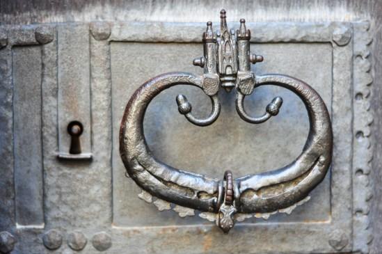 An Ancient Door Knocker With Castle Detail On An Iron Door