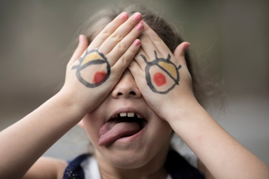 Little girl with cartoon eyes painted on her hands making silly