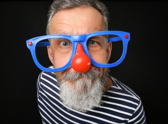 Mature man in funny disguise on dark background. April fool's da