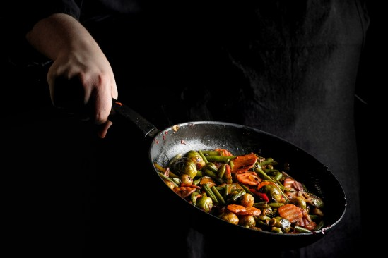 Chef is stirring vegetables in wok on black background.