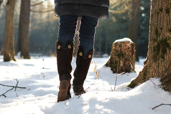 Pretty red-haired girl in the winter forest walks in the snow on a sunny day