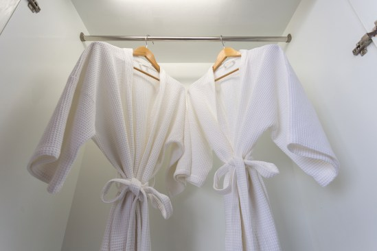 two off white color bathrobes hanging in closet room for copy space