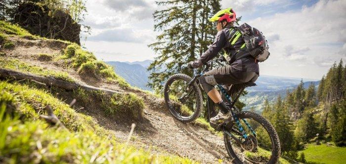 Biker in sella alla sua emtb in un tratto di salita (redbull.com).