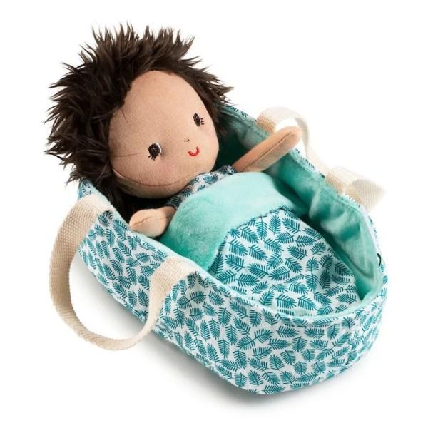 Le poupon en tissu Ari est présenté ici dans son couffin moelleux. C'est un adorable Bébé tout doux que l'on prend plaisir à câliner.