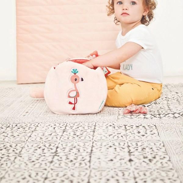 Petite fille assise présentant l'adorable sac à main Anaïs le Flamand rose. Sac à main pour enfant dès 18 mois. qui comporte de nombreux accessoires.