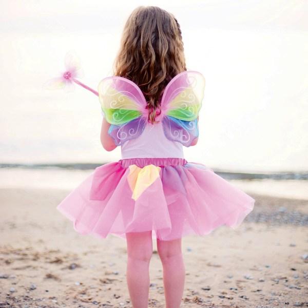 Ailes et baguette arc en ciel portées par une enfant de dos