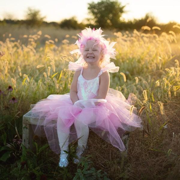 Robe de fée irisée et son halo portée par une enfant dans un champ