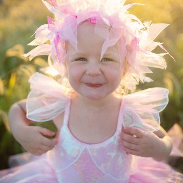 Robe de fée irisée et son halo portée par une enfant en gros plan dans un champ