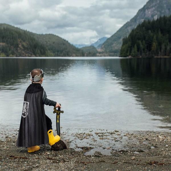 Cape cotte de mailles portée par un enfant près de l'eau, il regarde l'horizon