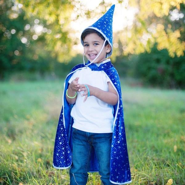 Cape de sorcier bleue avec des étoiles argentées brillantes portée par un enfant