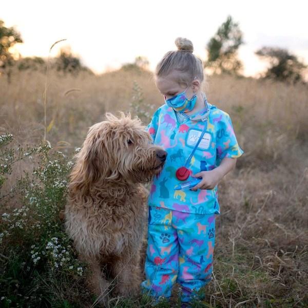 Un enfant porte le déguisement de vétérinaire et ses différents accessoires, un véritable chien est assis à côté